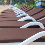 Row of sun loungers on a beach. Row of brown sun loungers on a beach with a blue and white fishing boat and red and yellow safety flag in the background stock image
