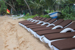 Row of sun loungers on a beach. Row of brown sun loungers on a beach with a blue and white fishing boat and red and yellow safety flag in the background royalty free stock image