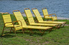 Row of sun loungers and deck chairs. Row of sun or beach loungers and deck chairs on the seashore of Florida stock images