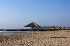Row of Sun Shade Umbrellas on Empty Beach Royalty Free Stock Image