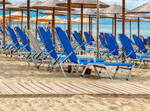 Row of sunbed at the beach with wooden path. Close Royalty Free Stock Photo