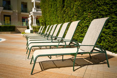 Row of sunbeds at poolside in luxurious hotel Stock Image