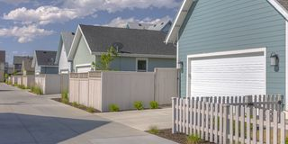 Row of sunlit houses with garages and white fences. Row of homes in sunny Daybreak, Utah under blue sky and clouds. The houses have white fences around yards royalty free stock images