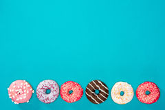 Row of sweet donuts. On blue background royalty free stock photos