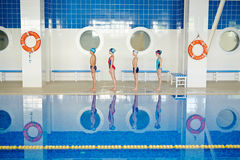 Row of swimmers. Row of little swimmers standing by pool Stock Images