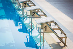 A Row Of Swimming Pool Starting Blocks At The pool Edge. Horizon Stock Photos