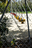 A row of swings at a park. A view of a row of swings at a park seen through a chain link fence Stock Photography