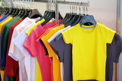 Row of t-shirts in store with empty space for text Royalty Free Stock Photos