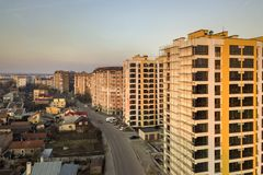 Row of tall apartment buildings and unfinished building with scaffolding along road with parked cars on blue sky copy space. Background. Aerial view royalty free stock images