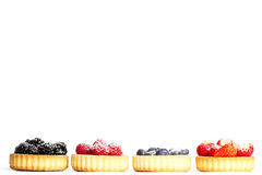 Row of tartlets with sugar covered wild berries Royalty Free Stock Photos