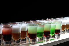 Row of tasty shots. Rows of beautiful multicolored bright green red orange white alcohol tasty sweet delicious shots drinks in drinking glasses standing on bar stock photos