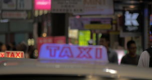 Row of taxi cars in night street. Taxi cars driving slow in row one after another on night road of Hong Kong. Illuminated signs on the top of the cabs stock video