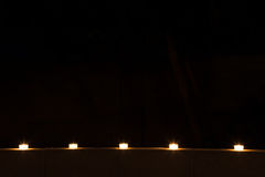 Row of tealights at night Royalty Free Stock Photos