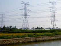 A row of telegraph pole near a river Stock Image