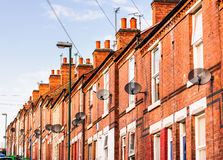 Row of terrace houses, almost all with satellite dishes. Royalty Free Stock Image