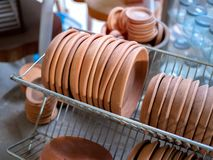 Row of terracotta dishes on old stainless steel shelf royalty free stock photos