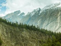 Row of textured mountains with green pine trees. Annapurna circuit trekking route. Nepal. Row of textured mountains with green pine trees. Scenic landscape with Stock Photography