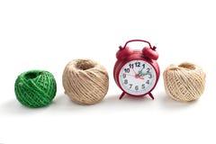 Row of thread and alarm clock Royalty Free Stock Photos