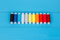 Row of threads laying on blue wooden background Royalty Free Stock Photos