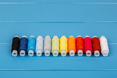 Row of threads lying on blue wooden background Royalty Free Stock Photography