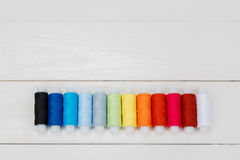 Row of threads lying on white wooden background. Stock Photography