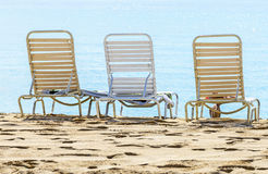 A row of three beach chairs Stock Photos