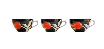Row of three black tea cups isolated Stock Photo