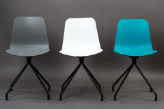 Row of three color plastic chairs isolated on gray background. Furniture series. Royalty Free Stock Images