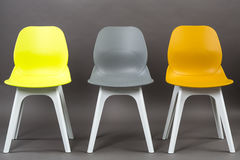 Row of three color plastic chairs isolated on gray background. Furniture series. Stock Photography