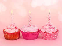 Row of three cupcakes with candles Stock Images