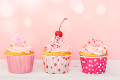 Row of three cupcakes with cream and decorations Stock Photography