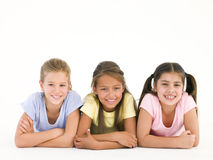 Row of three friends lying down smiling Royalty Free Stock Photo