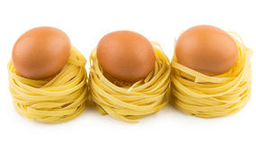 Row from three italian pasta in form nest and egg Stock Photography