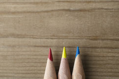 Row of Three Pencils in Red, Yellow and Blue. Three pencils lined in a row and pointing upwards towards wooden copy space, representing the primary colours model stock image