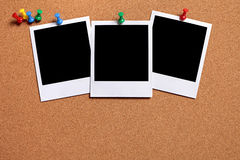 Row of three polaroid photo prints pinned to a cork board, copy space Royalty Free Stock Images