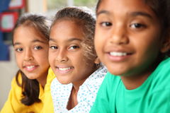 Row of three smiling young school girls. Three happy smiling young school girls sitting in a row in classroom, focus is on middle girl wearing white - Canon 5D Royalty Free Stock Photography