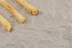 Row of three stick of french fries on gray crumpled paper. Row of three stick of tasty french fries on gray crumpled paper royalty free stock photography