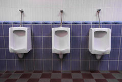 Row of three Urinals low light Stock Photo