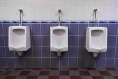 Row of three Urinals low light Stock Photo