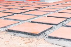 Row tile ceramic orange on floor install with cement in work construction renovation outdoor home.  Stock Photos