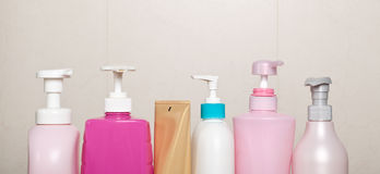 Row of toiletry bottles. Against bathroom wall Stock Image