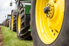 A row of tractor wheels. Parked up in a line on grass verge Stock Photo