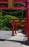 Row of traditional, red Torii and entrance path to japanese Jigoku Meguri Shinto Shrine between a green landscape. In Beppu, Oita stock photography