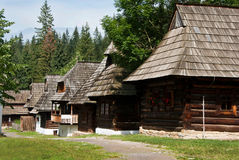 Row of Traditional Timber Houses with Wooden Roof. And forest in background. Central Europe - Slovakia Stock Photos
