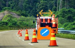 Traffic cone and sign for road user as reminder to be caution. Row of traffic cone and sign for road user as reminder to be caution royalty free stock photography