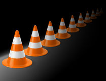 Row of traffic cones. Row of white and orange traffic cones on black background. Safety sign used to prevent accidents during road construction Stock Photo