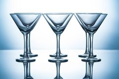 Row of transparent martini glasses on grey. With reflections royalty free stock image