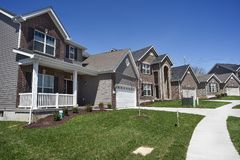 Row of two-story new residential homes for sale side by side in new subdivision grass yards and garages stock photos