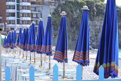 Row of umbrellas. A detail of a beach with closed umbrellas in italian riviera during spring Stock Photos