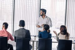 Row of unrecognizable business people sit in conference hall at business event. Diverse people sitting in a line at conference hall at corporate briefing royalty free stock image